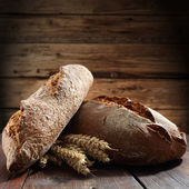 Bread on old wooden table — Stockfoto