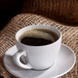 White cup of coffee on brown color — Stock Photo