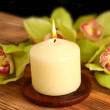 Royalty-Free Stock Photo: Candle on table with  orchid