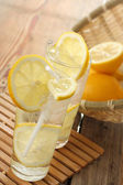 Cold water in glass and lemon — Stock Photo