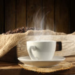 Coffee in cup and wooden background — Stock Photo