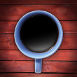 Blue cup of coffee on red table — Stock Photo
