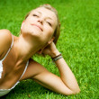 Beautiful healthy Young Woman lying on the green grass — Stock Photo #10603818