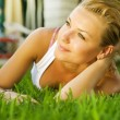 Stock Photo: Beautiful healthy Young Woman relaxing on the green grass