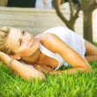 Beautiful healthy Young Woman relaxing on the green grass — Stock Photo #10603824
