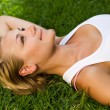 Stock Photo: Beautiful Healthy Young Woman Lying On The Green Grass