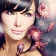Beautiful Healthy Woman with Orchid flower — Stock Photo #10604891