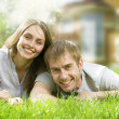 Happy Couple Near Their Home. Smiling Family Outdoor. Real Estat - Foto Stock