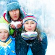 familia outdoors.happy familia con niño soplando snow.winter — Foto de Stock