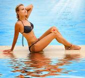 Tatil. güzel bir genç kadın bir havuz — Stok fotoğraf