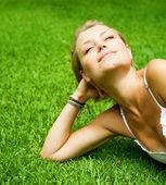Schöne gesunde junge frau, die auf das grüne gras liegend — Stockfoto