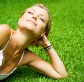 Beautiful healthy Young Woman lying on the green grass — Stock Photo