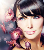 Beautiful Healthy Woman with Orchid flower — Stock Photo
