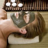 Spa. knappe man met een modder masker op zijn gezicht — Stockfoto