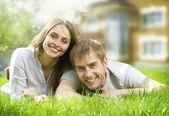 ευτυχισμένο ζευγάρι κοντά στο σπίτι τους. χαμογελώντας οικογένεια υπαίθρια. κερδη απο εκποιηση ακινητων — Φωτογραφία Αρχείου