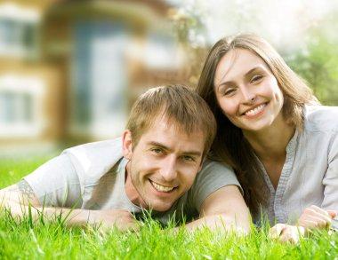 Happy Couple near their House. Smiling Family outdoor. Real Esta
