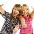 Portrait of happy teen girls showing thumbs up isolated one whit - Stock Photo