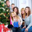 Foto de Stock  : Happy Big family holding Christmas presents at home.Christmas tr