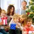 Photo: Happy Big family holding Christmas presents at home.Christmas tr