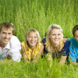 Happy Friends Outdoor Lying On A Green Grass — Stock Photo #10676265