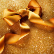 Stock Photo: Gold Ribbon Bow on Blinking Background Holiday Background.Gree