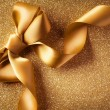 Royalty-Free Stock Photo: Holiday Background.Greeting Card.Gold Bow on a Blinking Backgrou