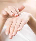 Female applying moisturizer to her Hands after bath. — Stock Photo