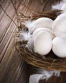 Huevos de pascua en el nido sobre fondo de madera — Foto de Stock