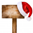 Wooden sign with Santa hat isolated on white - Stock Photo