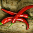 Red Hot Chili Peppers over wooden background — Stockfoto