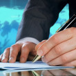 Businessman's hand with a pen. International business concept - Stock Photo