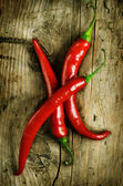 Red Hot Chili Peppers over wooden background — Stock Photo