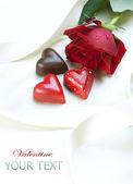 Alla hjärtans-kort. choklad hjärtan och röd ros — Stockfoto