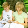 Two School Girls Reading The Book Outdoor — Foto Stock