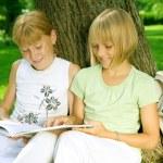duas garotas de escola, lendo o livro ao ar livre — Foto Stock