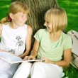 Two School Girls Reading The Book Outdoor — Stock fotografie