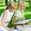 Two School Girls Reading The Book Outdoor — Stockfoto #10747013