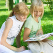 Foto Stock: Two School Girls Reading The Book Outdoor
