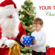 Santa Claus giving Christmas gifts to children — Стоковое фото