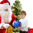 Santa Claus giving Christmas gifts to child — Stock Photo