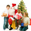 Santa Claus giving Christmas gifts to children — Stock Photo