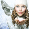 Christmas Girl. Winter woman Blowing Snow — Stock Photo #10747762