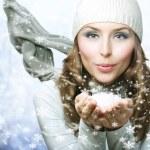 Christmas Girl. Winter woman Blowing Snow — Stock Photo #10747762
