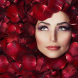 Beautiful Woman's Face and rose petals. Perfect Skin — Stock Photo