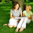 Royalty-Free Stock Photo: Mother And Daughter Reading The Book In A Park. Education Concep