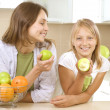 Happy Mother with Daughter eating Healthy food. Diet. Healthy Ea - Stock Photo
