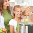 Happy Family making fresh apple and carrot juice — Stockfoto #10747957
