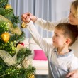 Kids decorating a Christmas tree with baubles in the living-room — Stock Photo