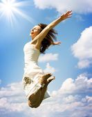Felice giovane donna saltando sopra un cielo blu — Foto Stock