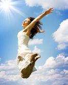 Mujer joven feliz saltando sobre cielo azul — Foto de Stock